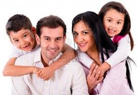 young family of four smiling with nice teeth